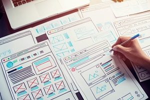 Web designers planning a website's pages using UX wireframes