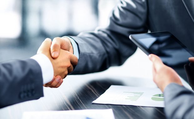 a handshake to close an insurance marketing services contract
