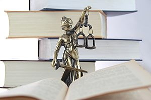 a lawyer statue with an open book next to it that contains good email marketing practices for law firms