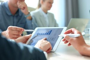 workers analyzing company data on their tablet to help develop a strategy for lead generation