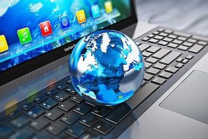 a globe on top of a computer symbolizing web marketing for dentists and how it is  important for any dental practice