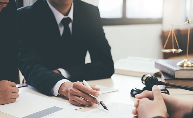 an attorney signing a document with a law firm marketing agency to discuss how digital marketing will be beneficial to his firm and book of clients