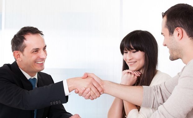 an insurance agent shaking hands with a couple who found his agency through a good insurance marketing campaign that has been running for several months