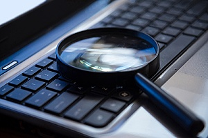 a magnifying glass on a keyboard representing search terms