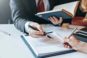 an attorney signing paperwork with a client who discovered the firm online